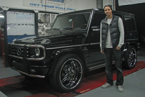 Stephen Curry is standing infront of his customized 2009 Mercedes Benz G55 .